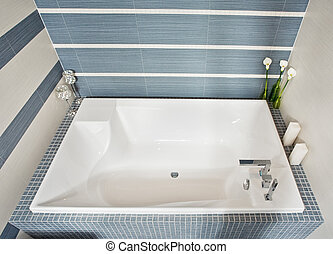 Modern bathroom in blue and gray tones with rectangular bath...