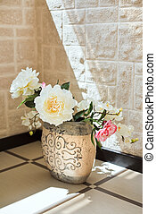 Peony flowers in pottery vase on the floor