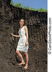 Lady in white sundress inside a deep black ground quarry -...