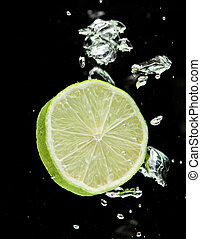 Lime lemon falling in water on black with air bubbles