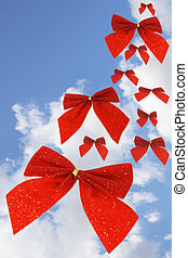 Red bow ribbons in the sky - Red bow ribbons falling against...