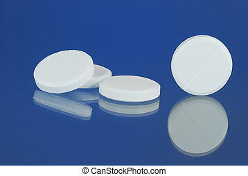 White tablets with reflection on blue background