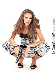 Young woman in harem pants posing with black pistol on white