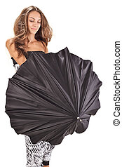 Young beautiful woman playing with black umbrella