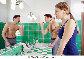 husband and wife brushing teeth in bathroom - caucasian...