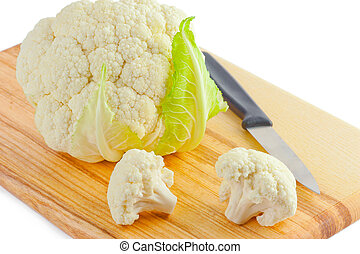Cauliflower cabbage and knife on wooden cutting board...