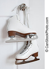 Figure skates hanging on a door knob - Elegant white figure...