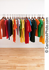 Variety of multicolored clothes on a rod - Variety of...