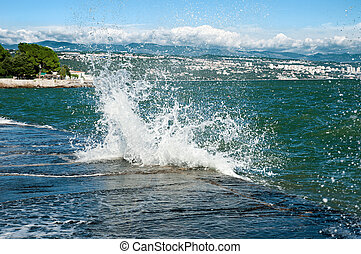 Wave breaks about seacoast - Wave with splashes breaks about...