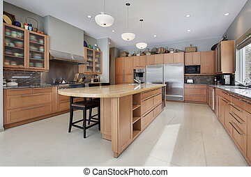 Large kitchen in luxury home with oak wood cabinetry