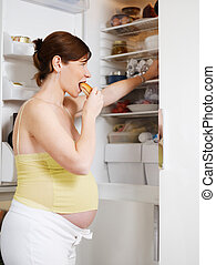 pregnant woman eating sandwich