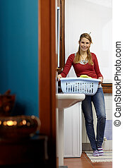 woman doing chores with washing machine - portrait of young...