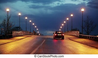 Cars driving by - Cars on a bridge with streetlights.