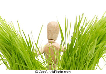 A wooden mannequin on green grass peeps