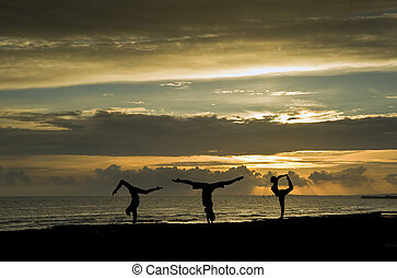 Silhouette of three fit young women doing stretching exercises on beach at sunset