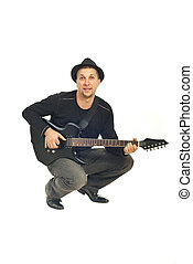 Mid adult man playing guitar - Mid adult man with hat...