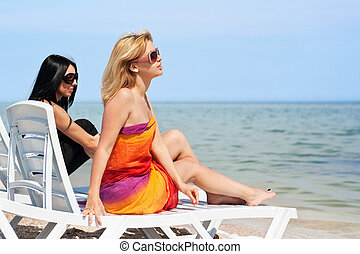 Two beautiful young women sitting on a sunbeds. Focus on...