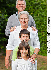 Grandparents with their children looking at the camera in...