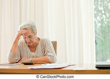 Retired woman calculating her domestic bills