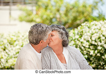 Man kissing his wife in the garden