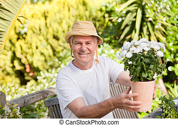 Senior man with flowers in his garden
