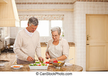 Senior couple cooking in the kitchen