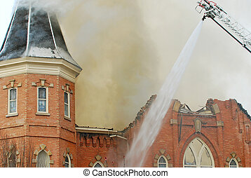 Old Church Burning - Firefighters putting water on a burning...