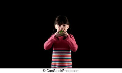 girl eating apple on black