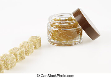 Body Scrub, row of pieces of brown sugar, on a white...