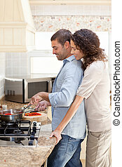 Woman hugging her husband while he is cooking at home