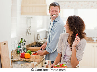 Beautiful woman looking at her husband who is cooking at...