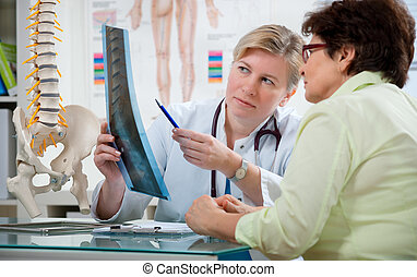 At the doctor's office - Doctor explaining x-ray results to...