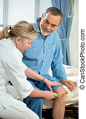 In hospital - Physician checking reflexes of an old man in...