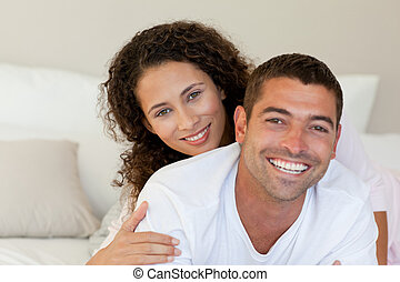 Pretty woman hugging her husband on their bed at home