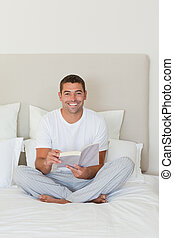 Man reading a book on the bed