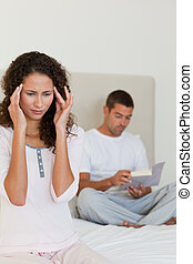 Woman having a headache while her husband is reading