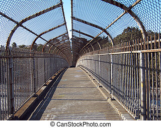 pedestrian overpass - inside view of a covered metal fence...