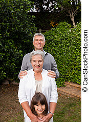 Grandparents with their granddaughter looking at the camera