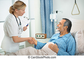 In hospital - doctor talking to a senior patient in hospital