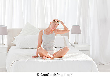 Beautiful woman practicing yoga on her bed at home
