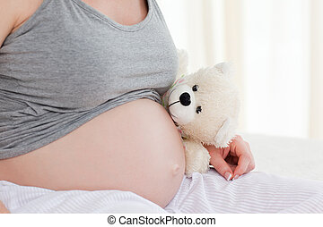 Pregnant woman with a cuddly toy