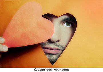 Face of young man peering from hole in heart-shaped closeup