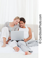 Adorable couple looking at their laptop on the bed
