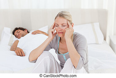 Attractive woman having a headache while her husband is...