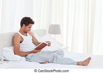 Man reading a book on his bed