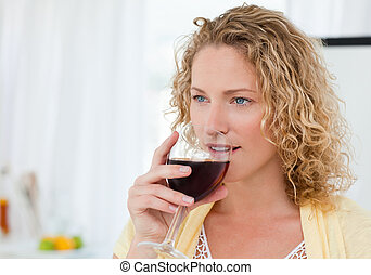Pretty woman drinking some wine at home