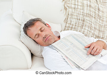 Exhausted man sleeping on the couch at home