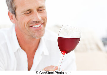 Handsome man drinking some red wine at home