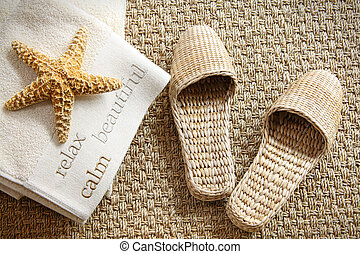 Spa slippers on seagrass carpet with towels and starfish