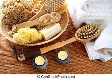 Spa brushes, sponges and soap on bamboo mat